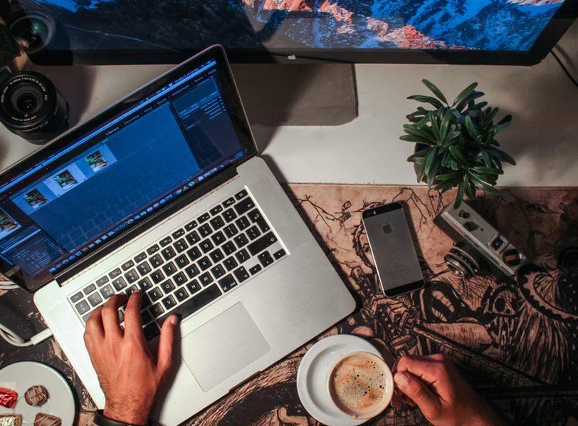 コーヒーを飲みながらパソコンを打つ男性