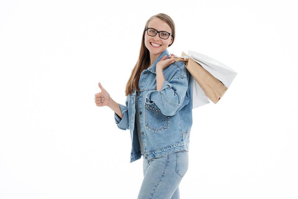 親指を立てている買い物帰りの女性