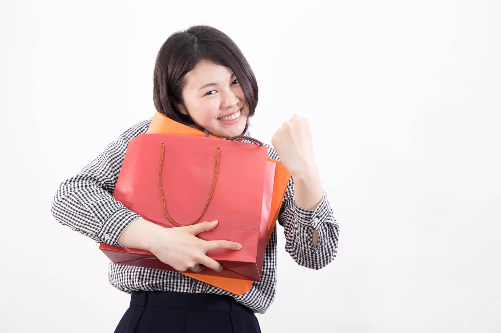 買い物袋を抱えてガッツポーズをとる女性